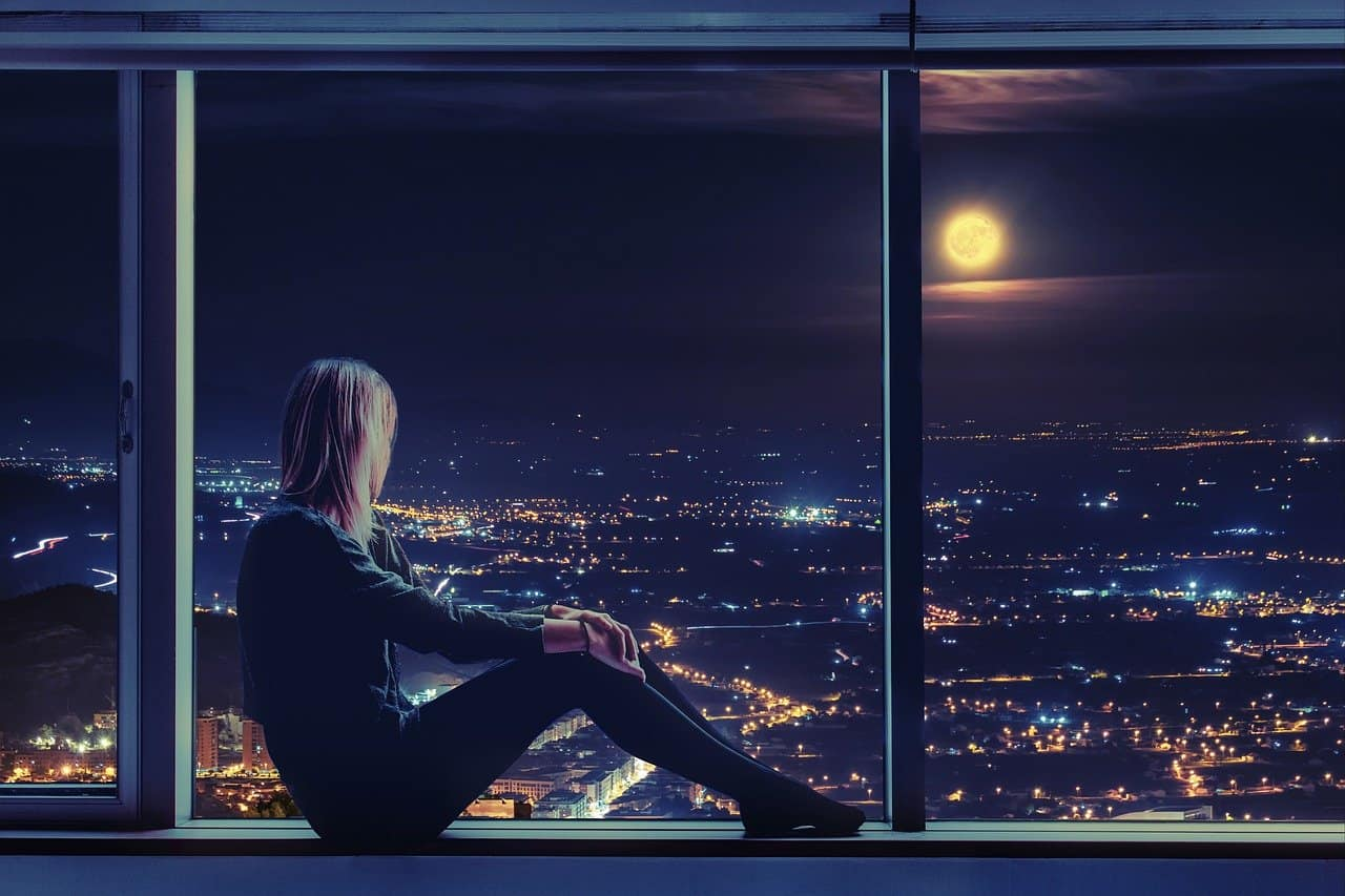 woman sitting by a large window